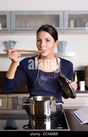Young housewife tasting her cooking as she prepares the dinner in her kitchen sampling directly from the pot on - Stock Photo