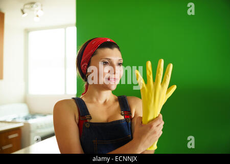 Young hispanic woman at home, doing chores and housekeeping work in kitchen, girl putting on yellow latex gloves - Stock Photo