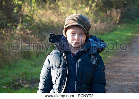 A happy 7 year old boy walking in the winter sun in Norfolk, photographed at Holkham UK - Stock Photo