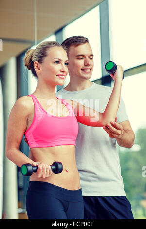 smiling young woman with personal trainer in gym - Stock Photo