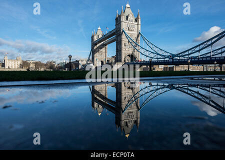 London, UK - 17 December 2014: Tower Bridge is reflected in a rain puddle near City Hall on a beautiful sunny day. - Stock Photo