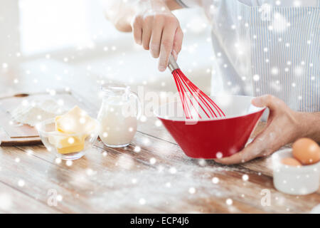 close up of man whipping something in bowl - Stock Photo