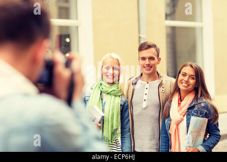 group of smiling friends taking photo outdoors - Stock Photo
