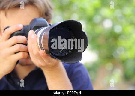 Close up of a photographer using a dslr camera with a green background - Stock Photo