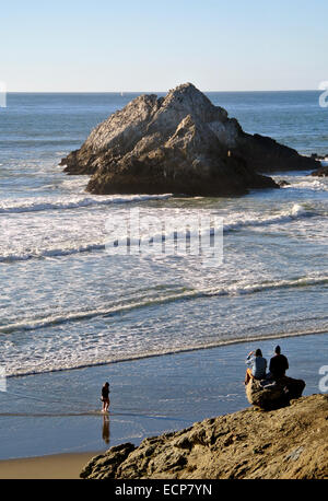 couple of friends watch the waves roll in on Ocean Beach near Seal Rock below the historic Cliff House on the California - Stock Photo