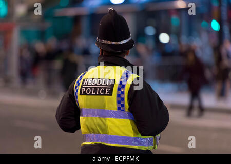 A police officer on patrol at night in Cardiff City Centre. Hundreds of revelers are out on weekends drinking alcohol. - Stock Photo