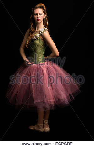 Young woman in a pink and green tutu on a black background. - Stock Photo