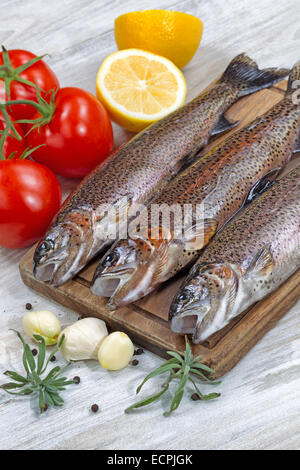 Vertical image of fresh wild trout being prepared, skin coated with oil, for cooking on server board. Herbs, tomatoes, - Stock Photo