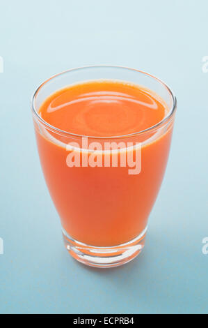 Carrot and apple freshly pressed juice in glass on light background. Healthy raw vegetable and fruit drink for healthy - Stock Photo