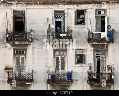 Six decaying balcony windows in Havana, Cuba with woman cleaning - Stock Photo