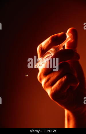 Threatening hand with syringe in blood-red light. - Stock Photo