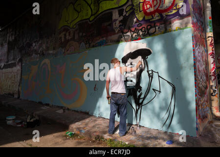 A young graffiti artist painting a mural under a bridge in amsterdam - Stock Photo