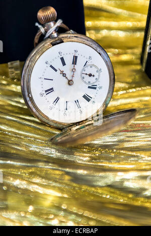 Image of a historic pocket watch on a gold background - Stock Photo