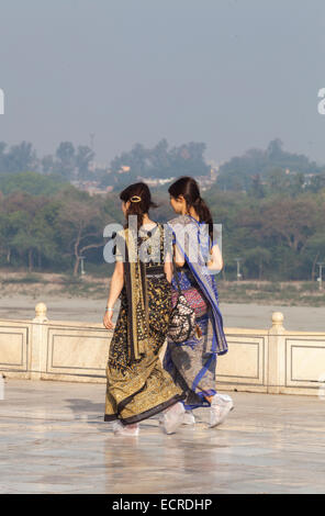 Two Japanese tourists wearing Indian outfit Saree walking with plastic wrapped shoes at Taj Mahal in Agra, Utter - Stock Photo