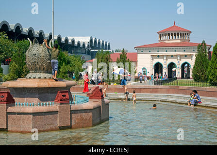 Children playing in fountain in front of the Chorsu Bazaar in the center of the old town of Tashkent, capital city - Stock Photo