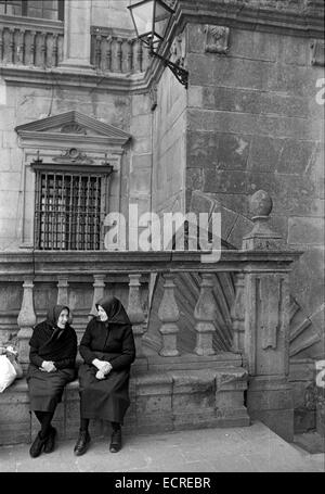 Two elderly women, dressed in a traditional way, seated converse near the Gothic Cathedral on August, 1977 in Santiago - Stock Photo