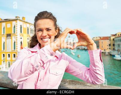 Happy young woman showing heart shaped hands framing santa maria della salute venice, italy - Stock Photo