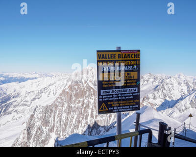 Warning sign for skiers by route to Vallee Blanche on Aiguille du Midi in French Alps. Chamonix-Mont-Blanc, Rhone - Stock Photo