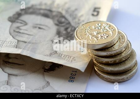 Stack of money, pound coins and £5 notes - Stock Photo