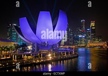 The purple illuminated ArtScience Museum and skyline with skyscrapers and high-rise buildings in Singapore at night - Stock Photo