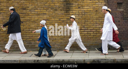 Some Muslim men and boys leaving the Regent's Park Mosque after prayers on Eid al-Fitr, at the end of Ramadan. - Stock Photo