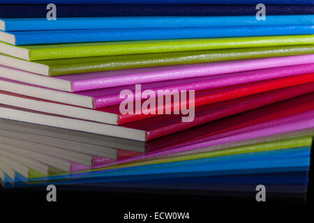 Twelve different colors diaries on a glass desk - Stock Photo
