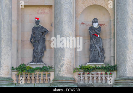 Lead statue by John Cheere of a Muse in a stone niches and wearing Santa Claus hat and tinsel - Stock Photo