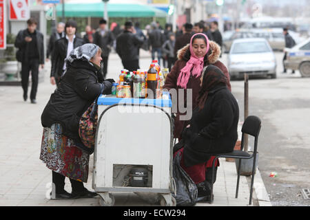 Woman selling drinks in Putin Avenue, the former Victory Avenue, in the centre of the Chechen capital Grozny, Russia. - Stock Photo