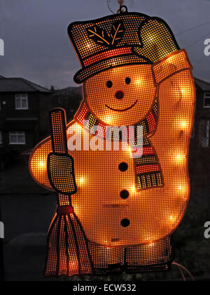 An electric snowman on a window, lit up for Christmas - Stock Photo