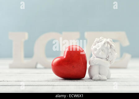 Statuette of small  angel with stone heart over light background - Stock Photo