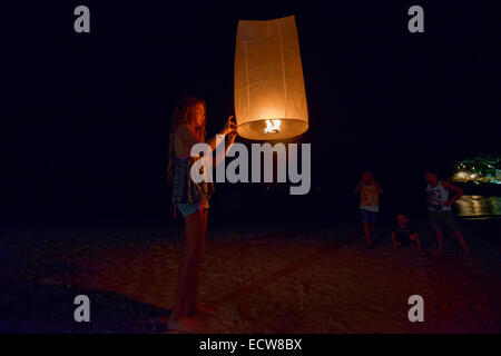 Lighting a paper lantern for the Yi Peng Festival, Chiang Mai, Thailand - Stock Photo