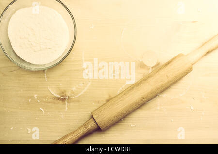Cutting board with a rolling pin and a bowl of flour - Stock Photo