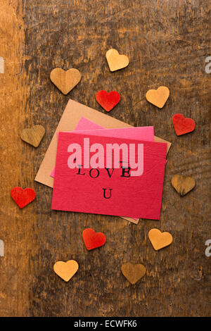 Handmade stamped valentine's day card with Love U stamped on it set on rustic wood - Stock Photo