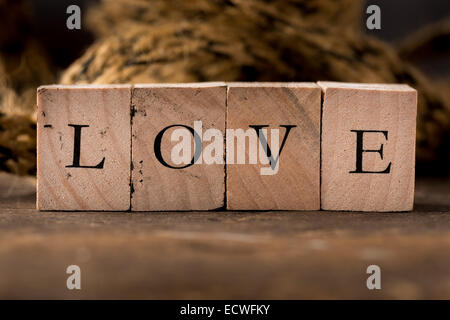 Stamping blocks with the word LOVE spelled out set on rustic wood - Stock Photo