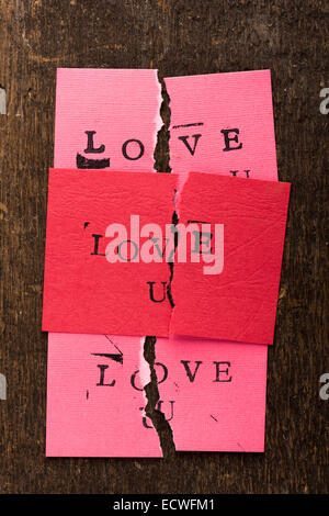 Handmade stamped valentine's day card with Love U stamped on it set on rustic wood torn in half - Stock Photo