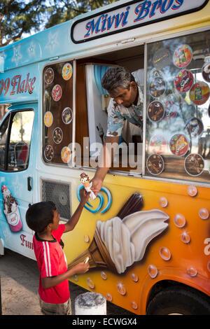Mauritius, Flic en Flac, Public Beach, ice cream van vendor passing icecream to child - Stock Photo