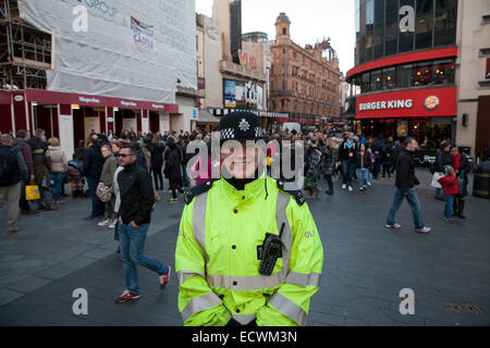 A police officer on duty amongst the crowds in Leicester Square on the last Saturday before Christmas - Stock Photo