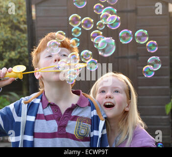 Children blowing bubbles; ginger haired boy with young sister - Stock Photo