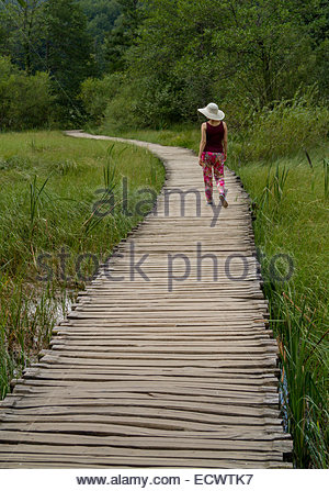 A women walking alone on a curved path. - Stock Photo
