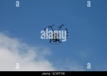 Aircraft type Dron photographed from the ground in flight and shooting events below it. - Stock Photo