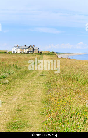 View of the Old Customs House, cliff top path, cliffs and the shoreline at Weybourne, north Norfolk - Stock Photo