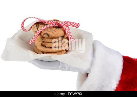 Santa Claus holding a plate with a stack of chocolate chip cookies tied with a ribbon. Only Santa's gloved hand - Stock Photo