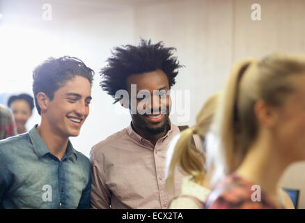 University students chatting during break in classroom - Stock Photo