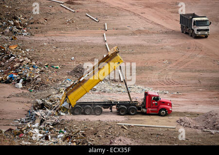 Dump truck unloading in a landfill - Stock Photo