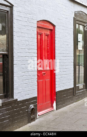 A newly painted red front door in an english town house - Stock Photo