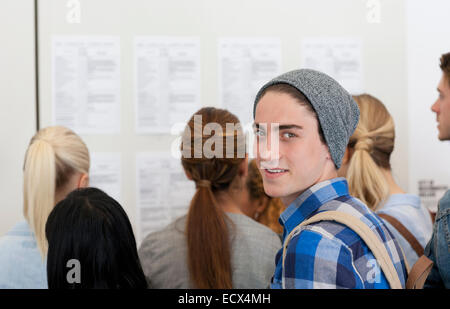 Male student smiling at camera while others read notice board - Stock Photo