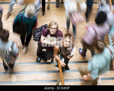 Male and female students looking at camera and standing in corridor during break - Stock Photo