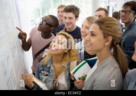 Group of smiling students holding books and looking at information board - Stock Photo