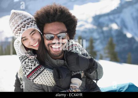 Portrait of happy couple hugging in snow - Stock Photo
