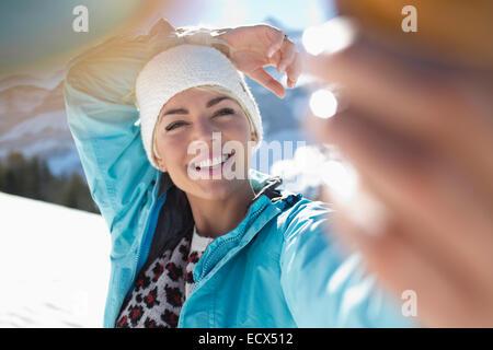 Happy woman taking selfie in snow - Stock Photo